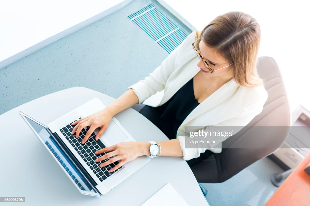 Beautiful well-dressed businesswoman using laptop in her office : Stock Photo