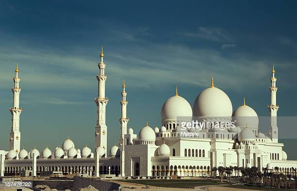 A beautiful white mosque on a partly cloudy day
