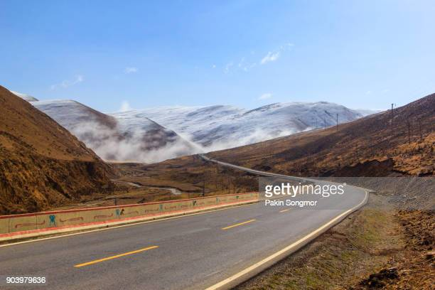 beautiful winter road in tibet under snow mountain - india summer stock-fotos und bilder