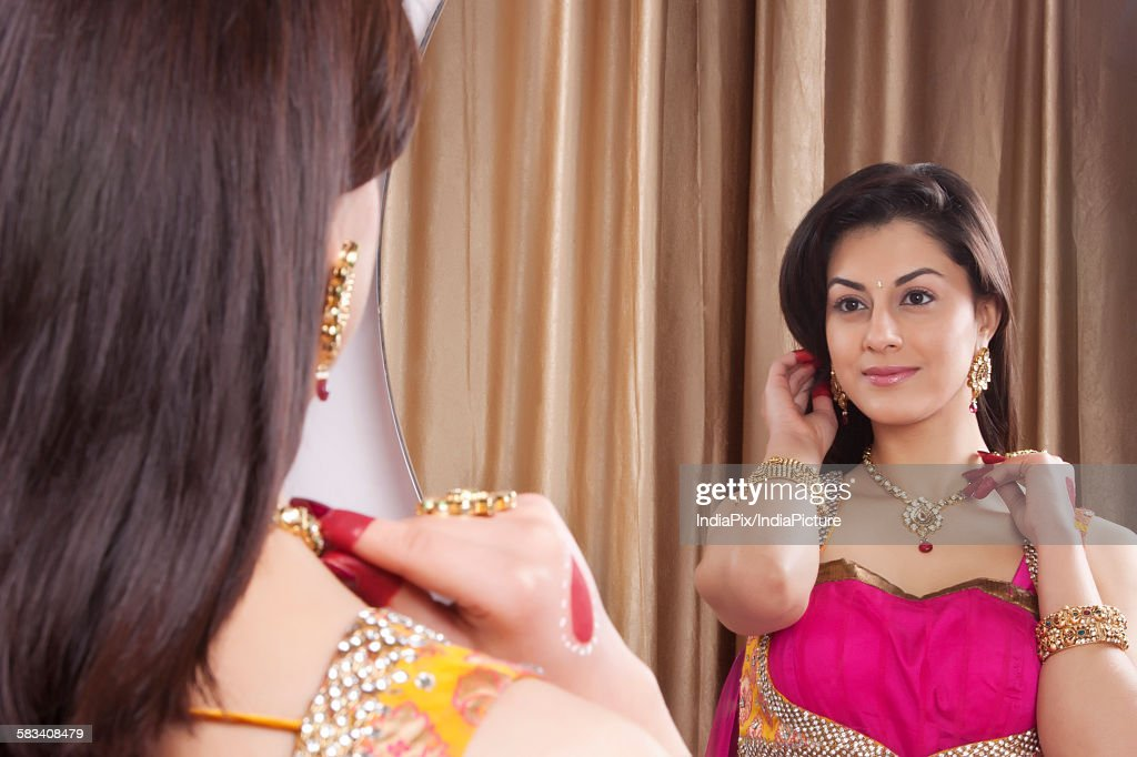 Beautiful woman admiring her jewelery : Stock Photo