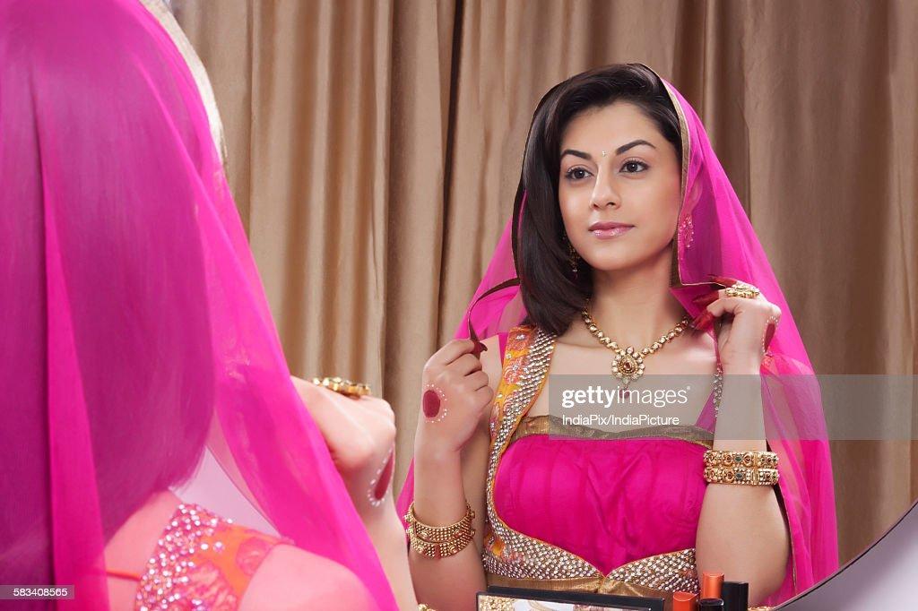 Beautiful woman admiring herself in the mirror : Stock Photo