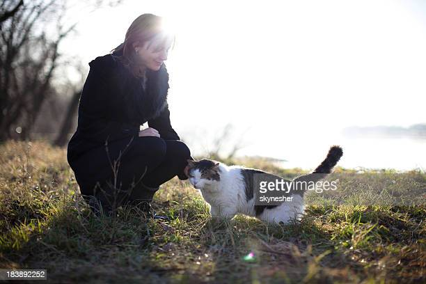 Beautiful woman and her cat surrounded by nature.