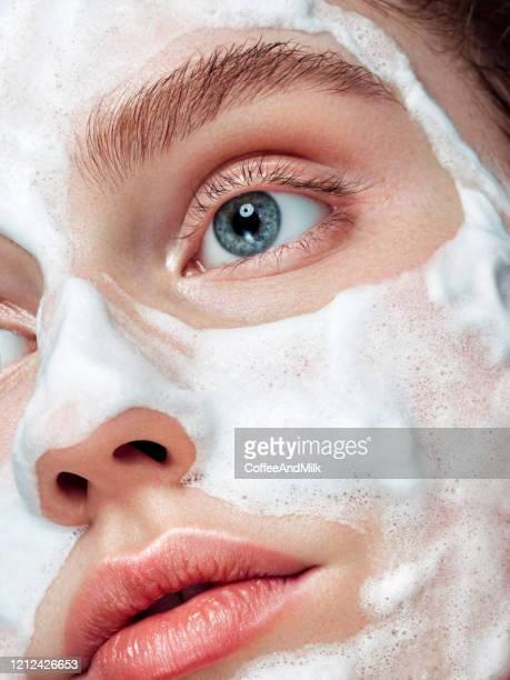 beautiful woman applying cleaning foam on the skin - brufoli foto e immagini stock
