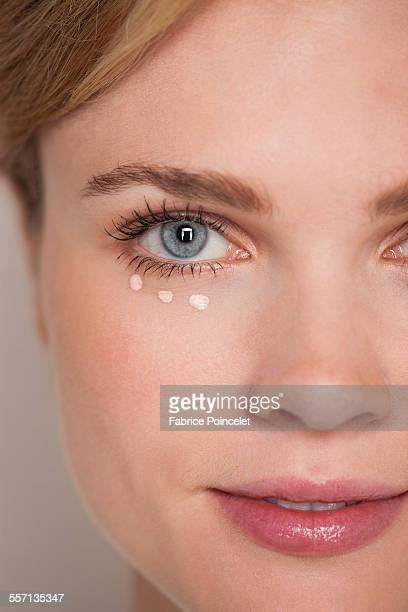 Beautiful woman applying concealer