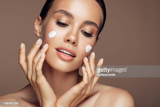 beautiful woman applying cream on her face - beautiful people stock pictures, royalty-free photos & images