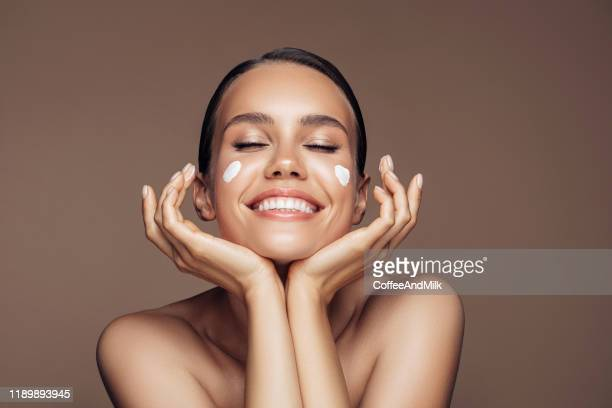 beautiful woman applying cream on her face - beauty stock pictures, royalty-free photos & images