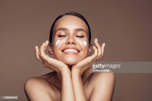 belle femme appliquant la crème sur son visage - beauté photos et images de collection
