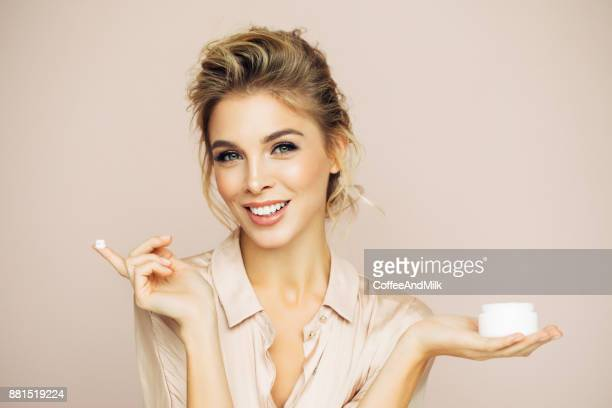 beautiful woman applying cream on her face - moisturiser stock pictures, royalty-free photos & images