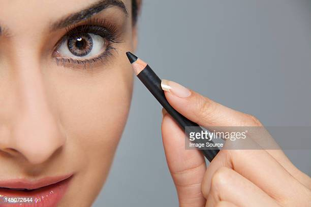 beautiful woman applying eyeliner - eye liner stock photos and pictures