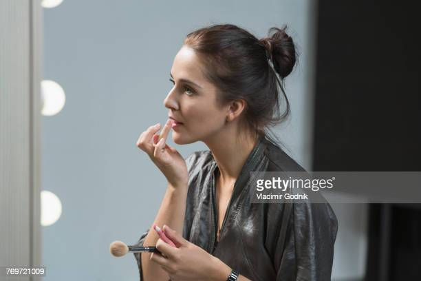 beautiful woman applying lip balm in front of dressing table - lip balm stock pictures, royalty-free photos & images