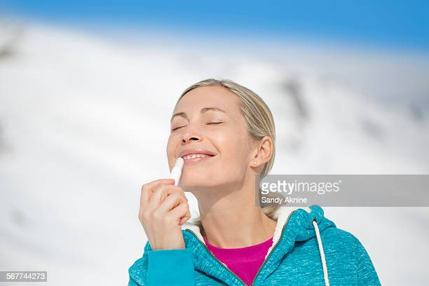 beautiful woman applying lip balm on her lips, crans-montana, swiss alps, switzerland - lip balm stock pictures, royalty-free photos & images