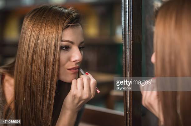 Schöne Frau benutzt Lippenstift vor dem Spiegel.