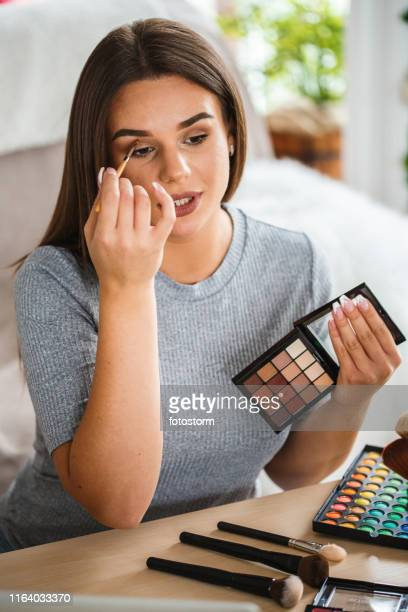 beautiful woman applying make-up - make up stock pictures, royalty-free photos & images