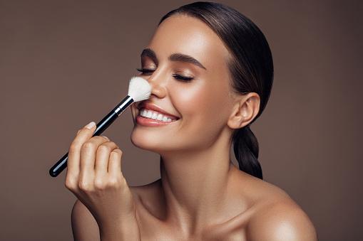 Beautiful woman applying make-up 1176520415