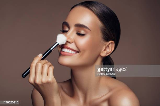 beautiful woman applying make-up - black hair stock pictures, royalty-free photos & images