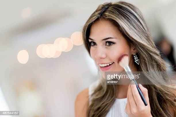 Beautiful woman applying makeup
