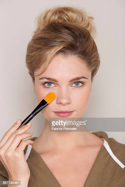 Beautiful woman applying make-up with a brush