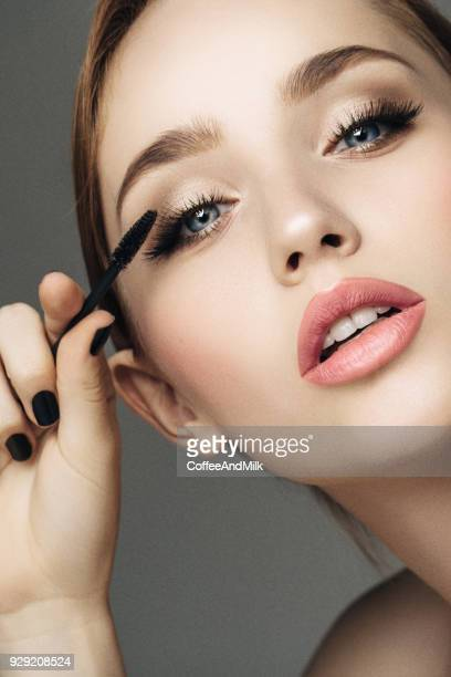 beautiful woman applying mascara - make up stock pictures, royalty-free photos & images