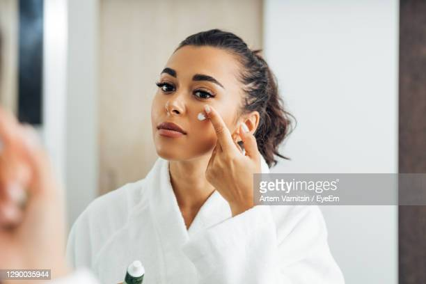 beautiful woman applying moisturizer on face - applying stock pictures, royalty-free photos & images