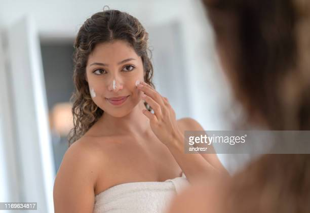 beautiful woman applying moisturizer on her face - applying stock pictures, royalty-free photos & images