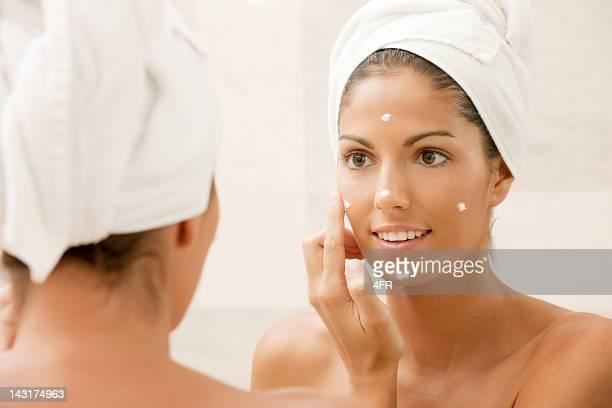 Belle femme, appliquer la crème hydratante sur son visage