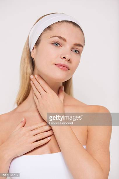 beautiful woman applying moisturizer on her neck - escote fotografías e imágenes de stock