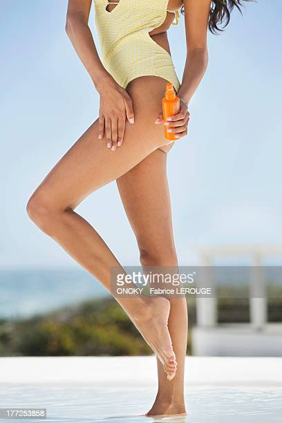 Beautiful woman applying suntan lotion on her thigh