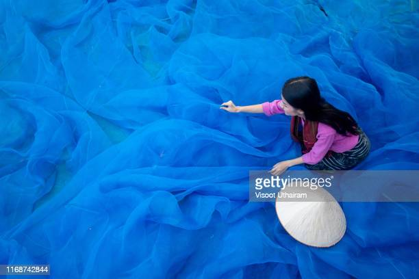 beautiful woman are cleaning the fishing nets at lake. - association of southeast asian nations stock pictures, royalty-free photos & images