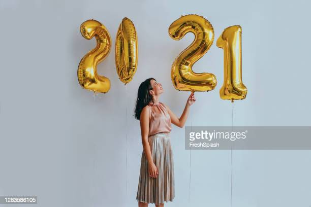 beautiful woman at a new year's party: playing with golden balloons (studio shot) - 2021 stock pictures, royalty-free photos & images