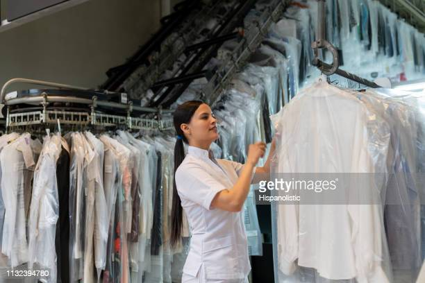 beautiful woman at an industrial laundry looking for a dry cleaned garment on conveyor belt - dry cleaner stock pictures, royalty-free photos & images