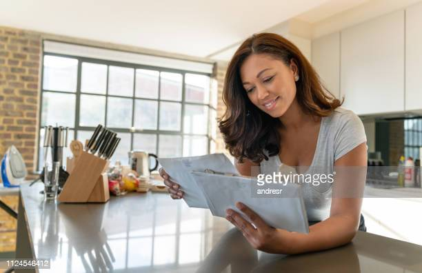 beautiful woman at home checking the mail - mail stock pictures, royalty-free photos & images