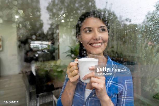 beautiful woman at home looking through the window on a rainy day enjoyng a cup of coffee - rain imagens e fotografias de stock