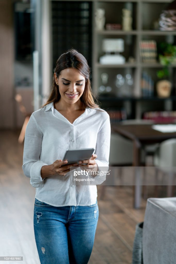 Beautiful woman at home reading a book on tablet looking very serene : Stock Photo