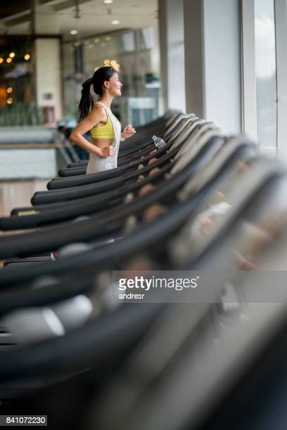 Beautiful woman at the gym running on a treadmill