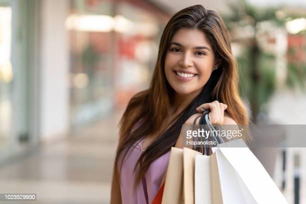 Beautiful woman at the mall enjoying shopping and looking at camera smiling while holding bags