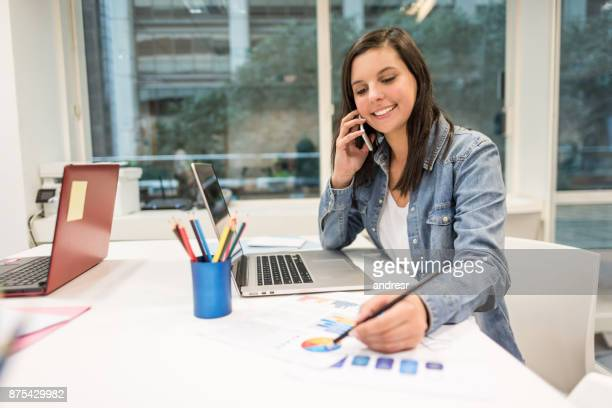 Beautiful woman at the office talking on her smartphone looking very happy and smiling
