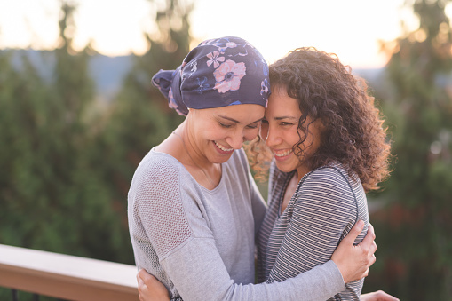 Beautiful ethnic woman battling cancer hugs her sister tightly 944834584
