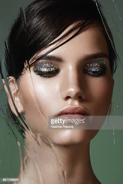 beautiful woman behind wet glass - eyeshadow stock pictures, royalty-free photos & images