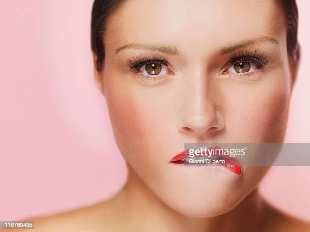 A beautiful woman biting her red painted lips