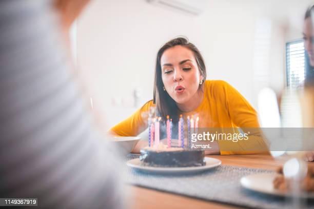 mooie vrouw waait kaarsen op verjaardagstaart - kaars stockfoto's en -beelden