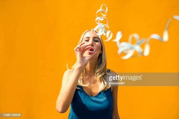 beautiful woman blowing confetti against yellow wall on sunny day - focus on background stock pictures, royalty-free photos & images