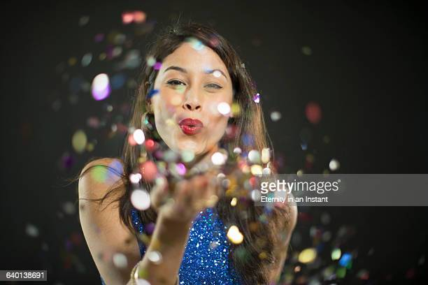 Beautiful woman blowing confetti at a party