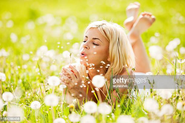 Beautiful woman blowing dandelions in the nature.