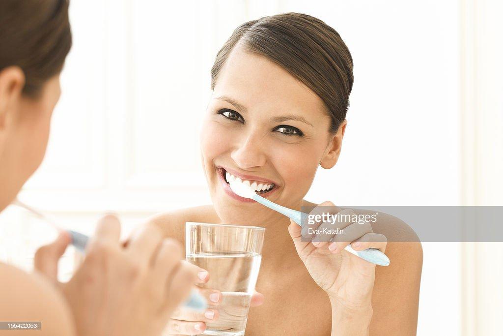 Beautiful woman brushing her teeth : Stock Photo