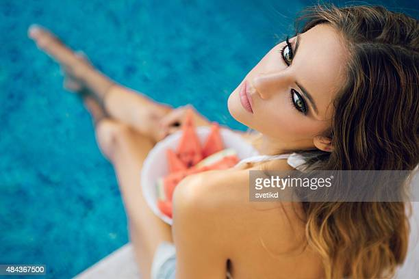 Beautiful woman by swimming pool.