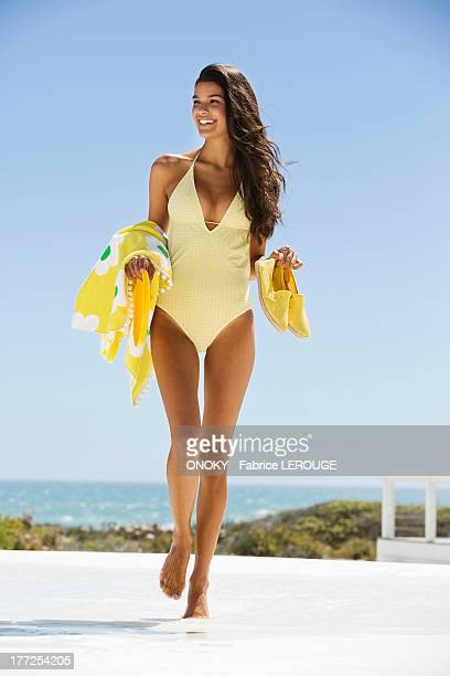 Beautiful woman carrying a towel and shoes on the beach
