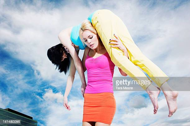 beautiful woman carrying another woman on shoulder