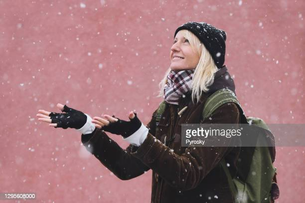a beautiful woman catches the first snowflakes on a walk - fingerless gloves stock pictures, royalty-free photos & images
