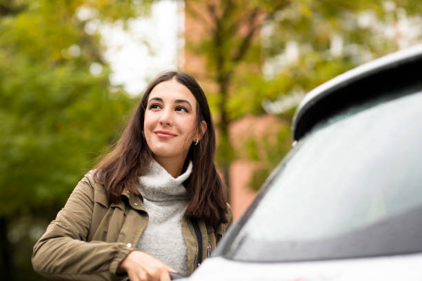 Beautiful woman charging rented electric car while smiling and looking away