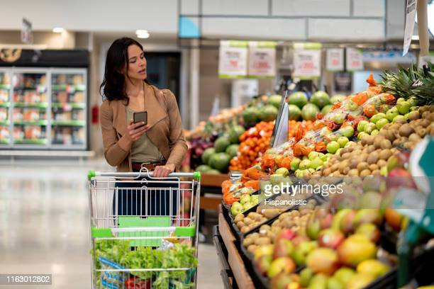 beautiful woman checking a shopping list on smartphone while looking for fruits on the vegetable display of a supermarket - produce aisle stock pictures, royalty-free photos & images